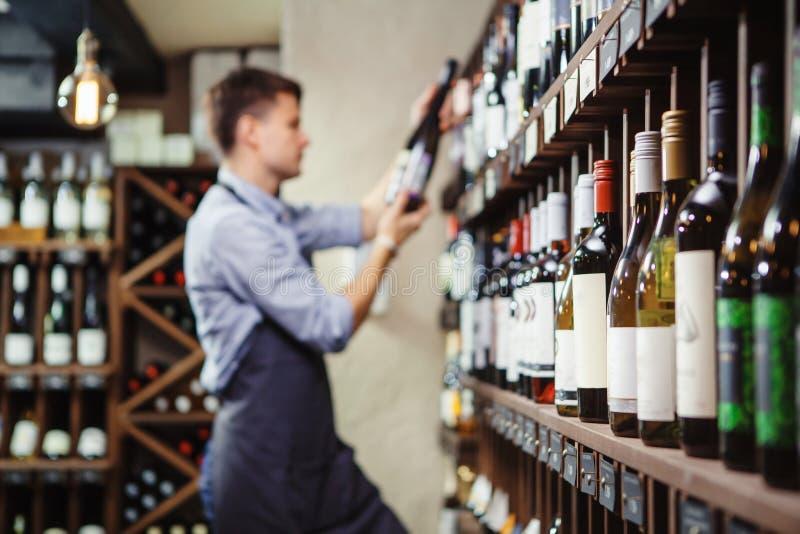 Estantes con el vino de la élite y el sommelier joven pensativo defocused fotos de archivo libres de regalías
