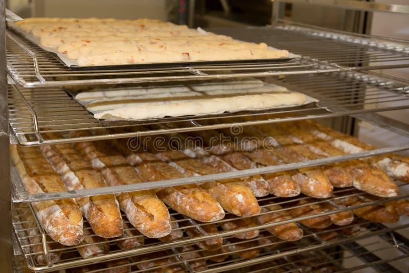 Estantes con los baguettes franceses cocidos en la exhibición de la panadería imágenes de archivo libres de regalías