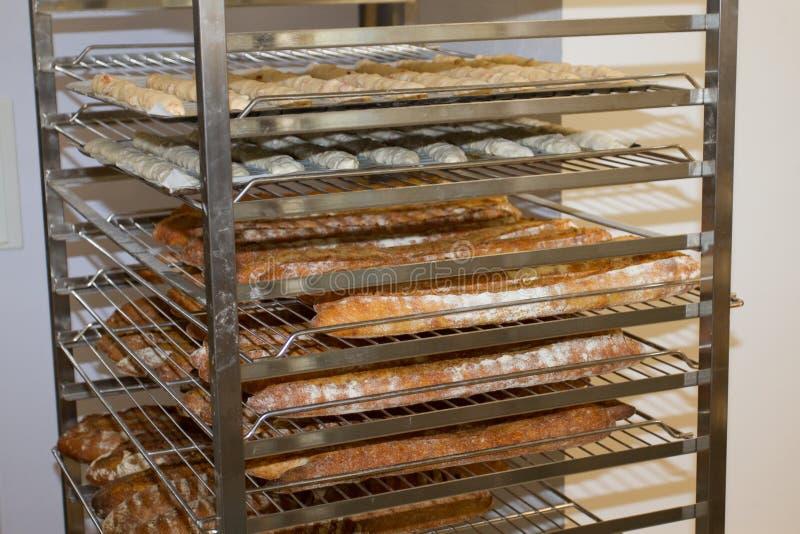 Estantes con los baguettes franceses cocidos en la exhibición de la panadería fotos de archivo libres de regalías