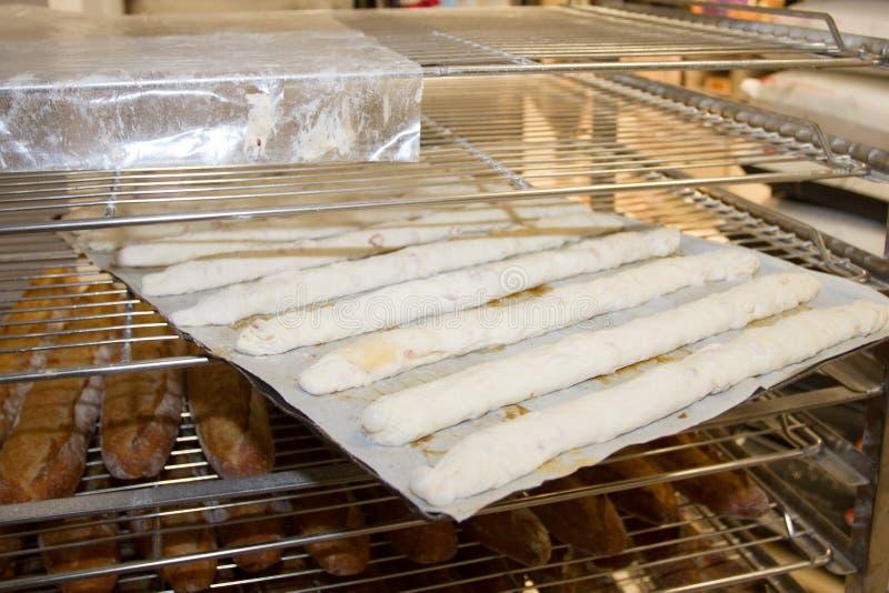 Estantes con los baguettes franceses cocidos y crudos en la exhibición de la panadería fotos de archivo