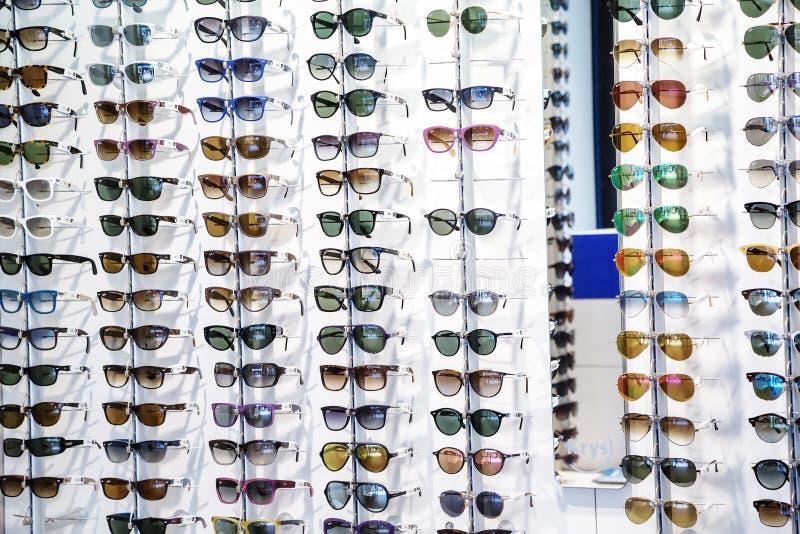 Estantes de gafas de sol en la exhibición en una tienda de las gafas imagen de archivo libre de regalías