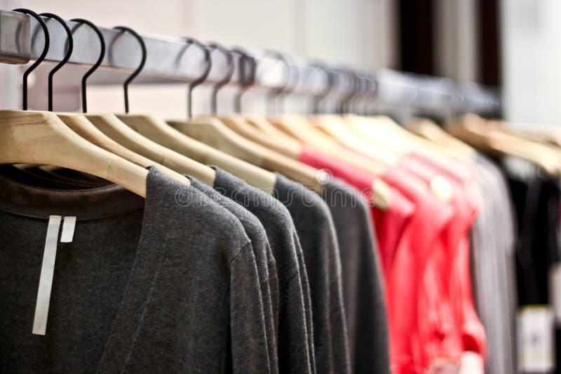 Estantes de los suéteres y de las camisas que cuelgan en un almacén imágenes de archivo libres de regalías