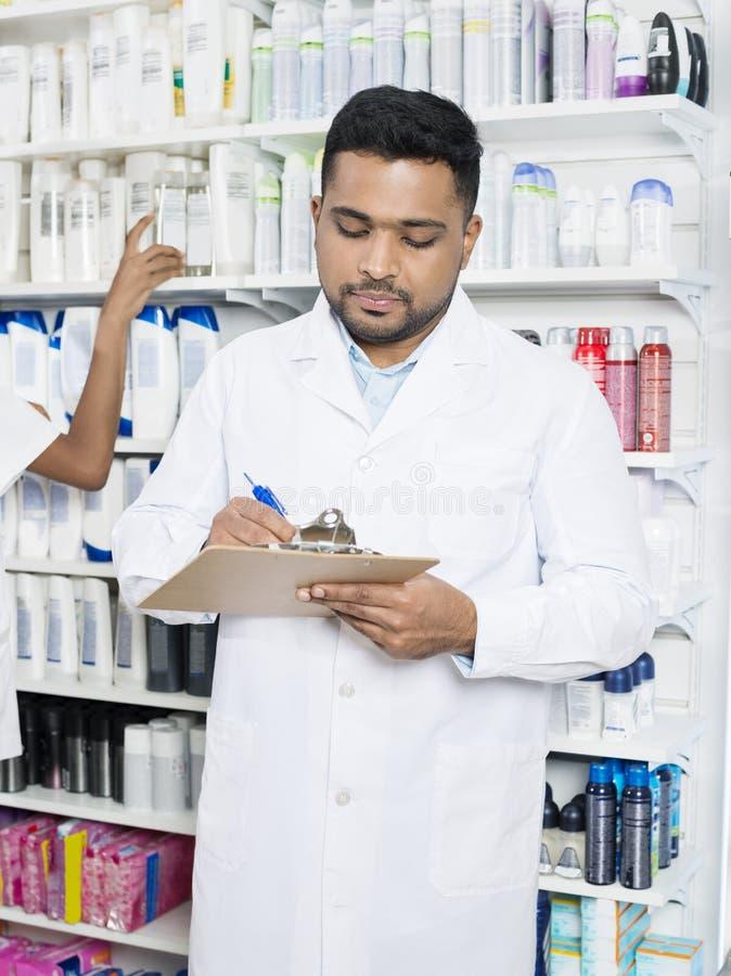 Estantes masculinos de Holding Clipboard Against del farmacéutico fotos de archivo