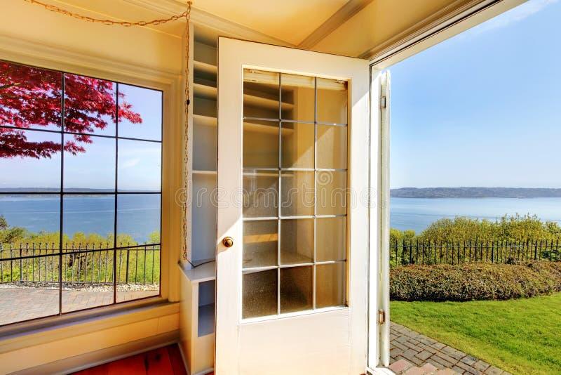 Estar aberto da sala de visitas ao pátio traseiro com opinião da água. foto de stock