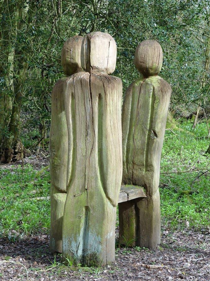 Estar cinzelou as figuras que cercam o banco na caminhada da floresta imagem de stock