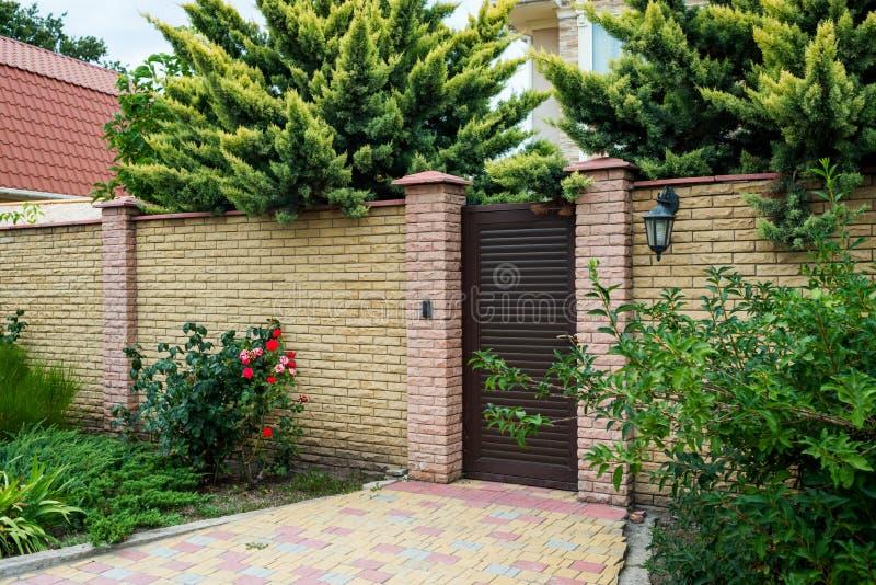 Estasi il gruppo della casa con un wicket e un recinto di pietra circondati dai cespugli e dagli alberi verdi fotografia stock