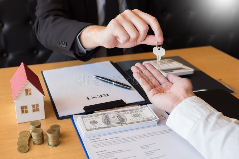 Estate agent giving house keys customer sign agreement property for sale, Buying and selling homes concept.  stock photo
