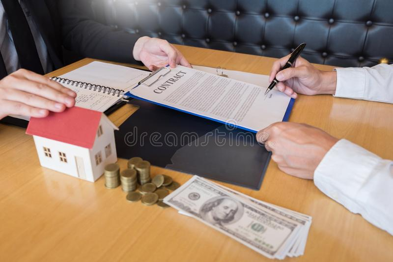 Estate agent giving house keys customer sign agreement property for sale, Buying and selling homes concept. Estate agent giving house keys customer sign royalty free stock photography