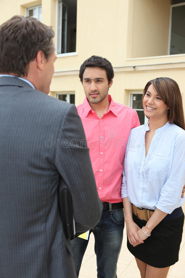 Estate agent meeting couple. For viewing stock photo