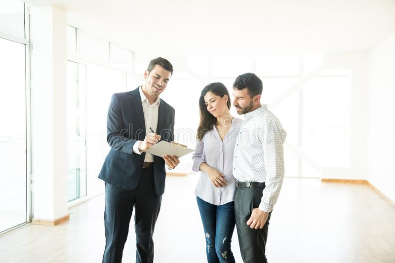 Estate Agent Reading Contract For Couple In New Home. Confident estate agent reading contract for mid adult couple in new home royalty free stock photos