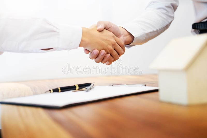 Estate agent shaking hands with customer after contract signature as successful agreement in real estate agency office. Concept o stock photo