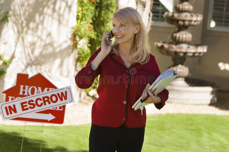 Estate agent using mobile phone. At in front yard of house, portrait stock image
