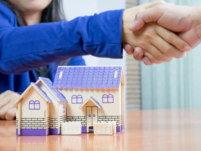 Estate agents join hands with buyers. After agreeing to sell the house successfully stock images