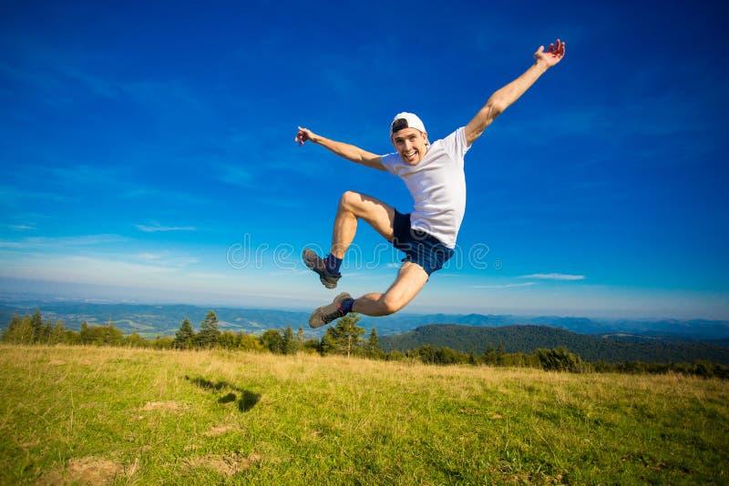 Estate che fa un'escursione in montagne Il giovane uomo turistico in cappuccio con le mani su sopra le montagne ammira la natura fotografia stock libera da diritti
