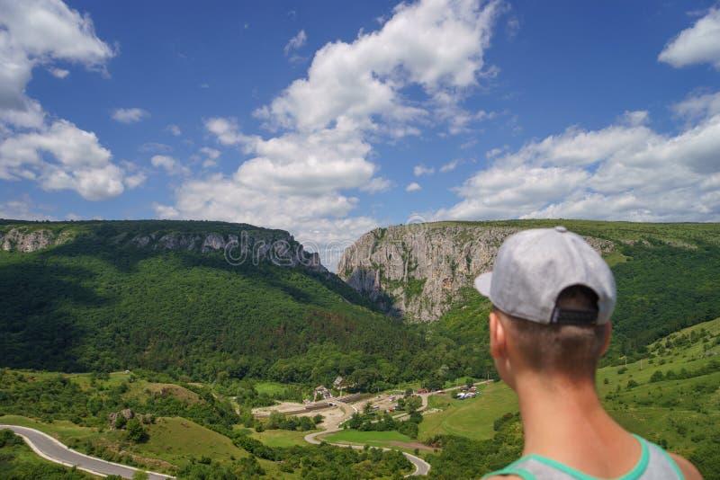 Estate che fa un'escursione nelle montagne Giovane uomo turistico in un cappuccio che considera montagna fotografia stock