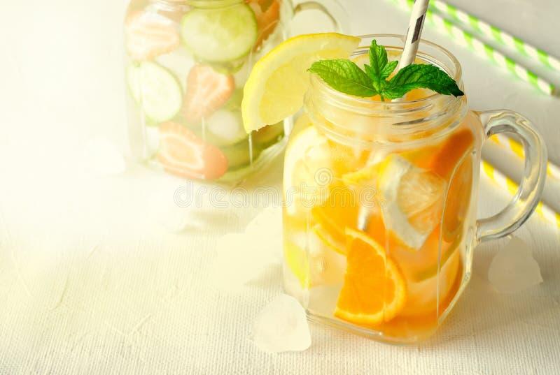 Estate che rinfresca le bevande ghiacciate con l'arancia, il limone, il cetriolo e la fragola su fondo bianco fotografia stock