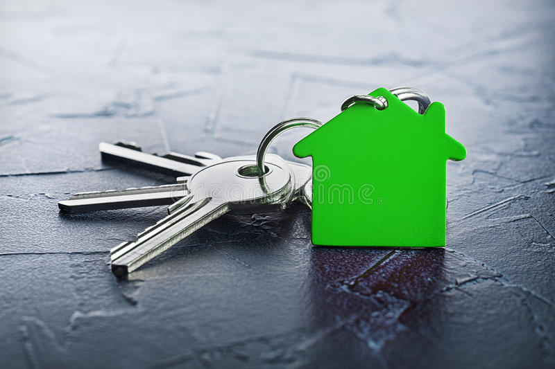 Estate concept with key, green keychain with house symbol, ecotechnologies. Estate concept with key, green keychain with a house symbol, ecotechnologies royalty free stock photography