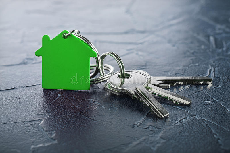 Estate concept with key, green keychain with house symbol, ecotechnologies. Estate concept with key, green keychain with a house symbol, ecotechnologies stock image