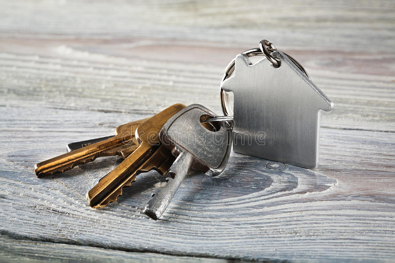 Estate concept with key, keychain with house symbol. Estate concept with key, keychain with a house symbol royalty free stock image