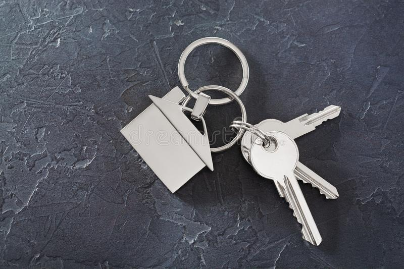 Estate concept with key, keychain with house symbol, stone background. Estate concept with key, keychain with house symbol, old stone background stock photography
