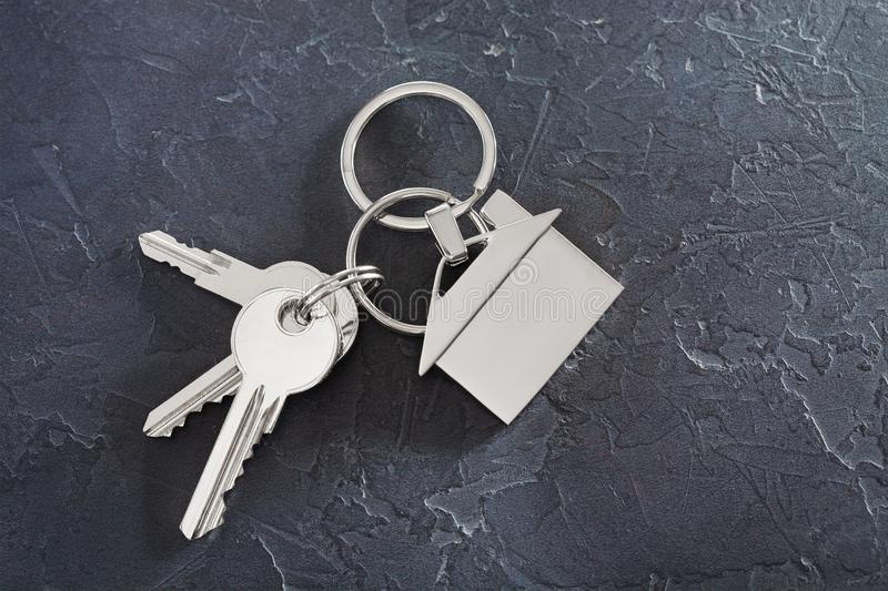 Estate concept with key, keychain with house symbol, stone background royalty free stock photos