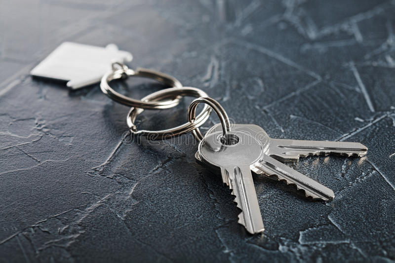 Estate concept with key, keychain with house symbol, stone background. Estate concept with key, keychain with a house symbol, stone background royalty free stock images