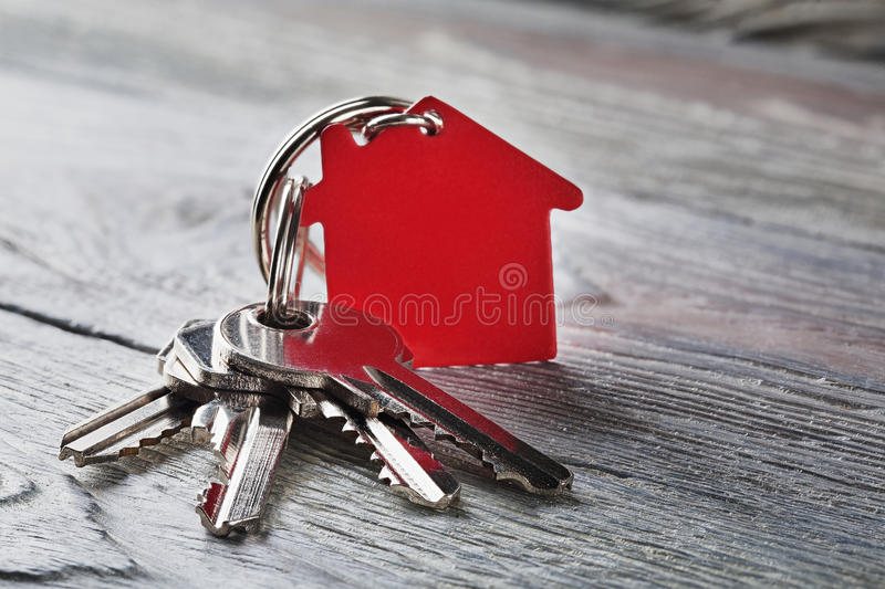 Estate concept with key, red keychain with house symbol. Estate concept with key, red keychain with a house symbol royalty free stock photo