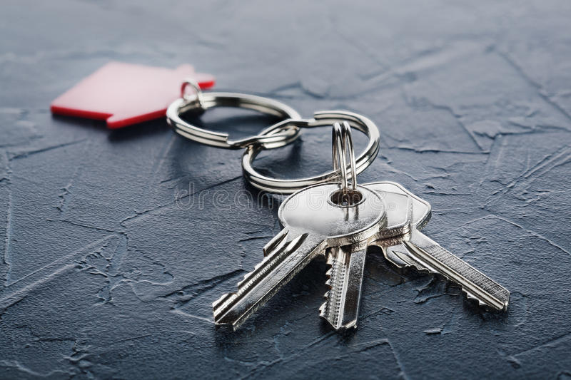 Estate concept with key, red keychain with house symbol, concrete. Estate concept with key, red keychain with a house symbol, concrete stock photo