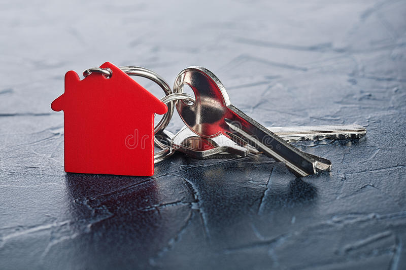 Estate concept with key, red keychain with house symbol, concrete. Estate concept with key, red keychain with a house symbol, concrete royalty free stock images