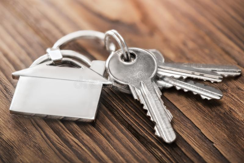 Estate concept, keychain with house symbol, key on wooden background royalty free stock images