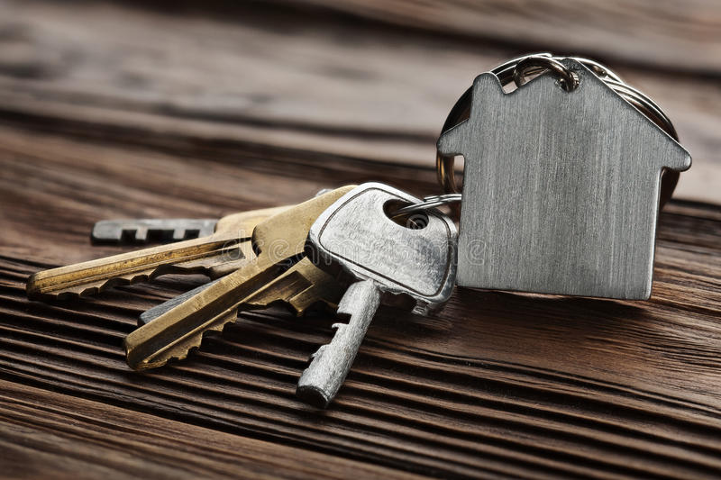 Estate concept, keychain with house symbol, key on wooden background. Estate concept, keychain with house symbol, key on a wooden background stock image