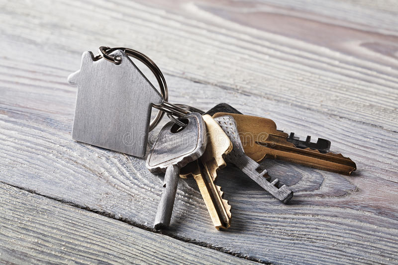 Estate concept, keychain with house symbol, key on wooden background. Estate concept, keychain with house symbol, key on a wooden background stock images
