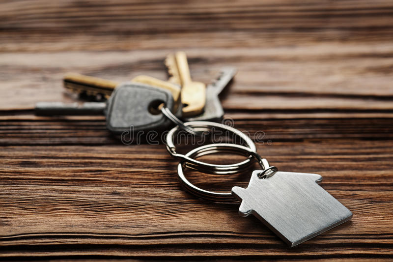 Estate concept, keychain with house symbol, key on wooden background. Estate concept, keychain with a house symbol, key on wooden background royalty free stock photography