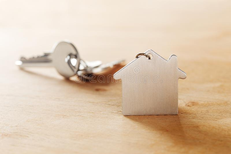Estate concept with symbol of house, key on wooden background royalty free stock photo