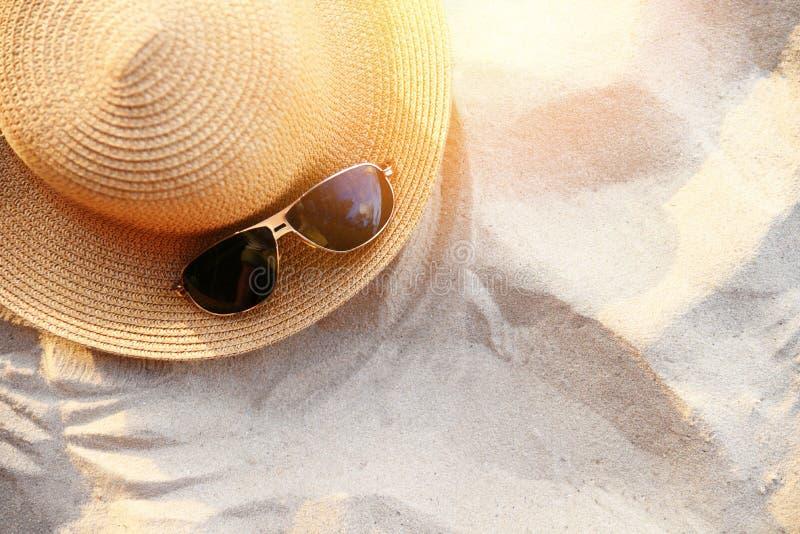 Estate del cappello/fasion cappello di paglia ed accessori degli occhiali da sole sul fondo del mare della spiaggia sabbiosa immagini stock