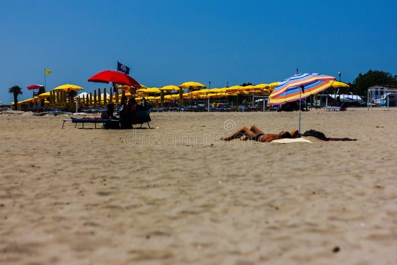 Estate della spiaggia il momento di abbronzatura belle donne dei giochi variopinti degli ombrelli riempire le spiagge di intero m immagini stock libere da diritti