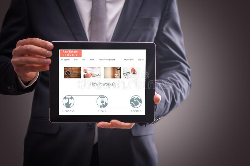Estate expert web site On Tablet. Real Estate Agent man Showing estate a web site On Tablet royalty free stock images