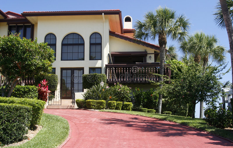 Estate Home. Lovely home in southwestern Florida with wide red paved driveway, arched windows, Spanish-style, and tropical landscaping royalty free stock images
