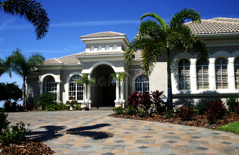 Estate Home. Beautiful estate home in tropics, with wide tiled driveway, columns, bright, blue sky stock image