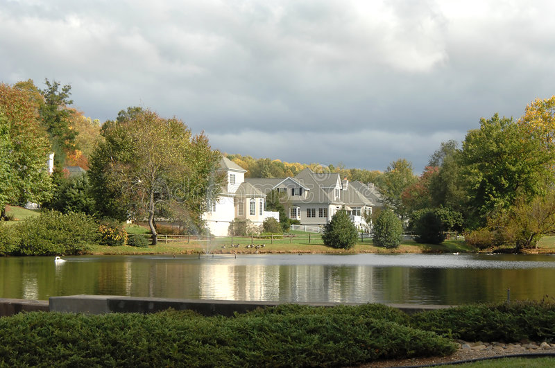 Estate Homes by Lake. Estate homes line the shores of a small lake. Homes are reflected in the still waters. Duck swims in left corner royalty free stock photos