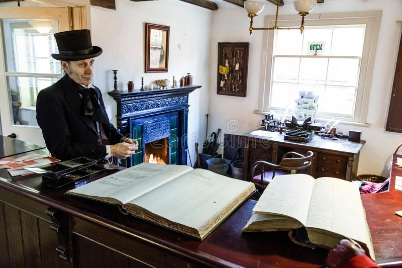 Estate office at Blists Hill Museum. TELFORD, UK - CIRCA 2013: An actor dressed in Victorian costume, The Estate Office, Blists Hill Museum, Shropshire, UK royalty free stock photos