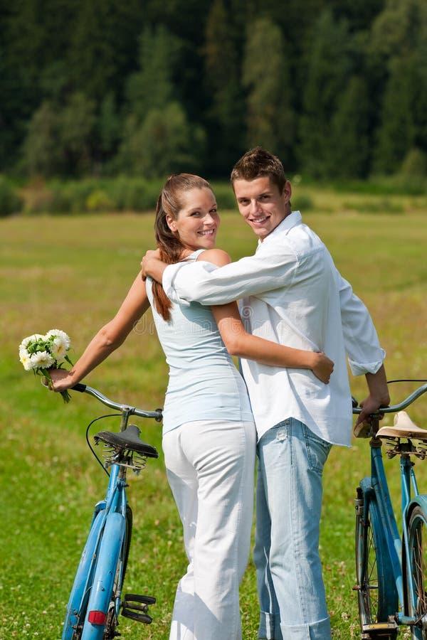 estate romantica del prato delle coppie della bici immagine stock libera da diritti