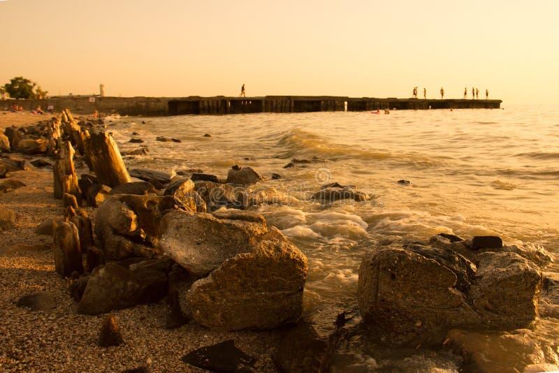 Estate, tramonto della spiaggia dal mare Nei precedenti, un frangiflutti da cui la gente salta nella ram Sulle pietre enormi ante fotografia stock