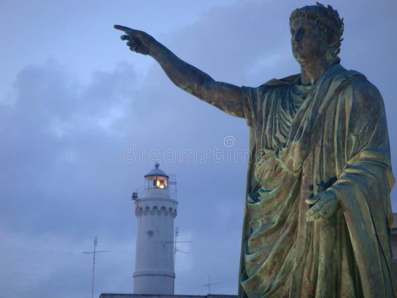 Estatua antigua del emperador Nero con en distancia la extremidad de un faro a la puesta del sol en la ciudad de Anzio en Italia foto de archivo
