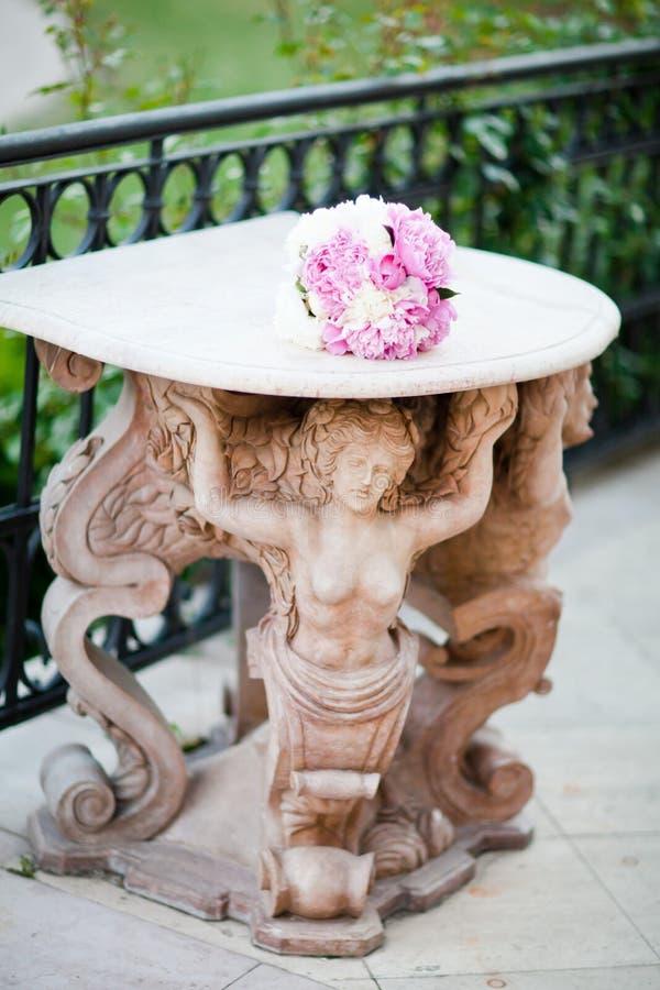 Estatua antigua que apoya una tabla con casarse el ramo foto de archivo libre de regalías