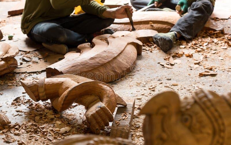 Estatua brazo y del pájaro de madera de Garuda con los reparadores que cincelan la madera para los proyectos de la restauración e fotos de archivo