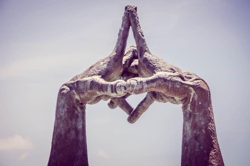 Estatua con las manos entrelazadas en parque imagenes de archivo