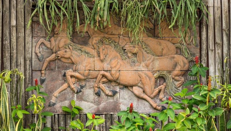 Estatua corriente de los caballos en la pared de bambú fotografía de archivo libre de regalías
