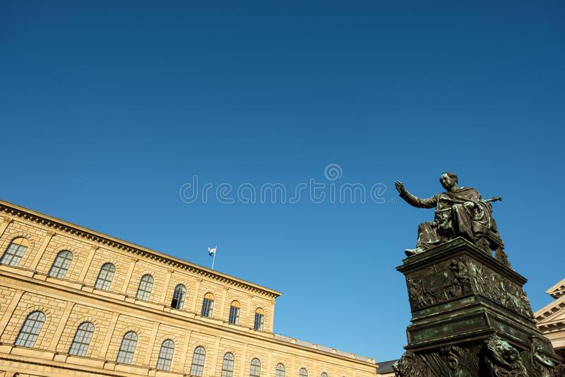 Estatua de Bronce de Max Joseph con el edificio de la residencia en Munich fotos de archivo