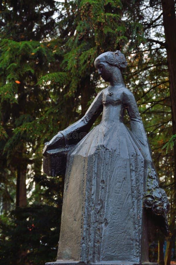 Estatua de bronce moderna de una mujer con las flores fotografía de archivo